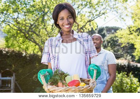 Portrait of young woman holding a basket of freshly harvested vegetables in garden