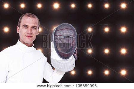 Swordsman holding fencing mask against composite image of orange spotlight