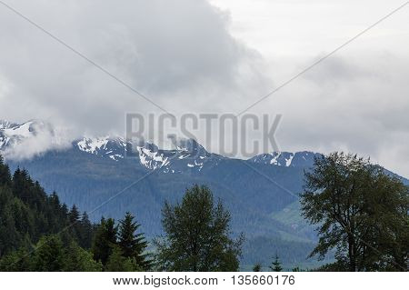 Snow capped mountains in background of evergreen covered hills in Alaska