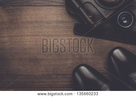 brown shoes and film camera on the wooden table