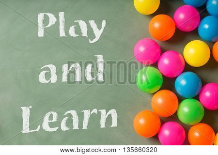 Green chalkboard with play and learn inscription and colorful plastic balls
