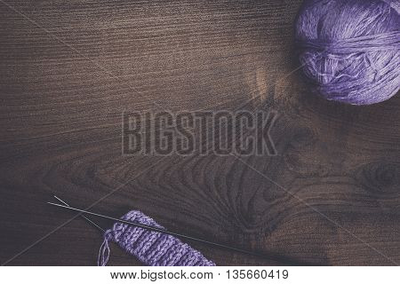knitting needles and balls of threads on wooden background