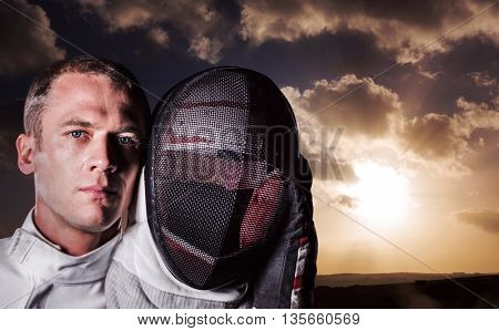Close-up of swordsman holding fencing mask against cloudy sky