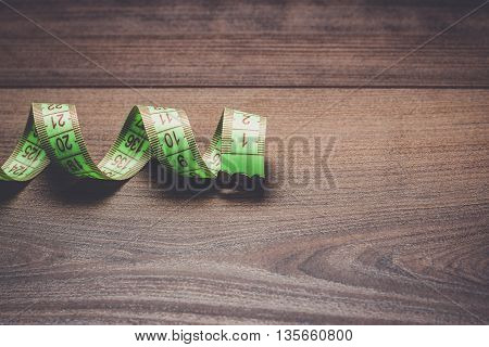 measuring green  tape on the wooden background