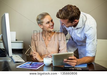 Young colleagues looking at each other while using digital tablet at desk in office