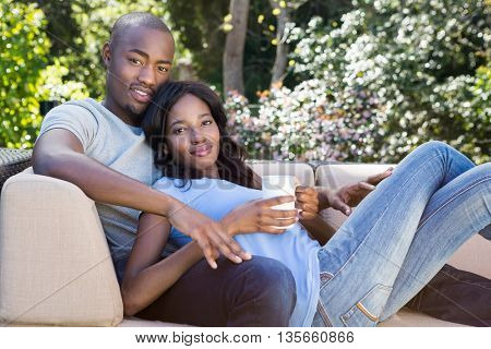 Portrait of young couple relaxing on the sofa and holding coffee mug in the park