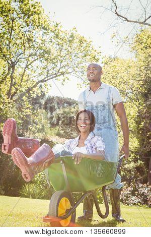 Young man giving woman a ride in the wheelbarrow in their garden