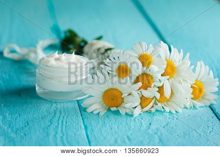 Cosmetic cream with camomile flower for a body and face on blue wooden table.