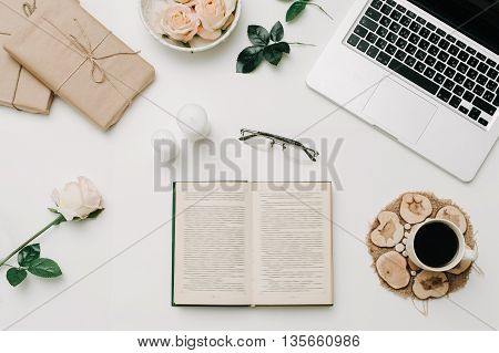 Opened book with glasses and coffee. White background.