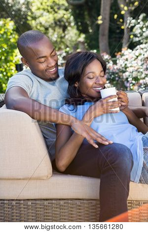Young couple relaxing on the sofa and having coffee in the park