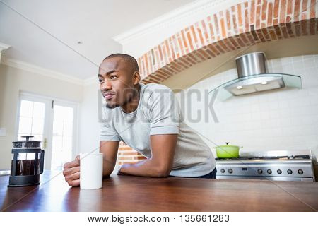 Young man leaning on the table and holding coffee mug in the kitchen