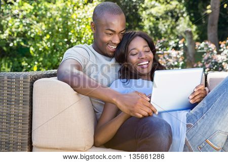 Young couple relaxing on the sofa and using digital tablet in the park