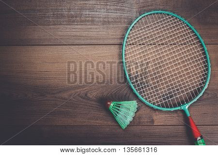 shuttlecock and badminton racket on wooden background