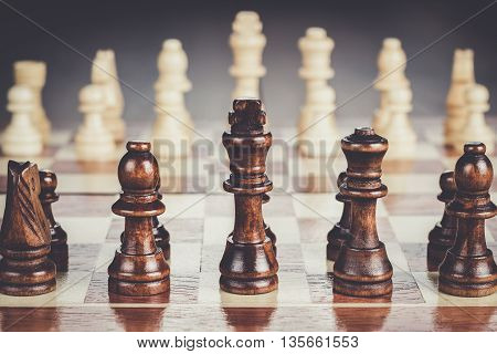 chess board with figures on the brown table background