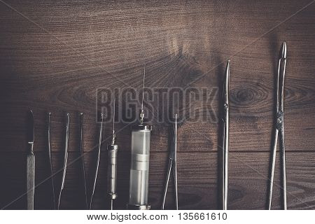 surgical armaments on the brown wooden table background