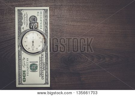 time and money concept on wooden background