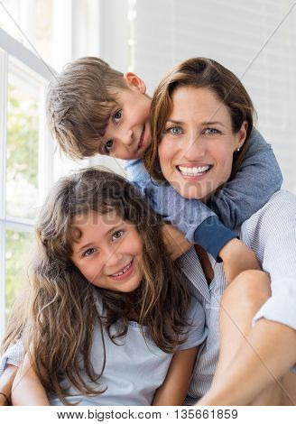 Son and daughter embracing mother. Mother enjoying with children on a bright sunny morning. Portrait of happy smiling mom with her children at home looking at camera. Happy family embracing.
