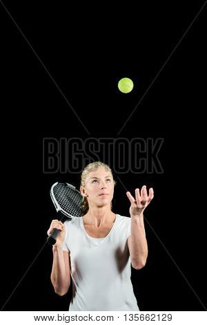 Tennis player holding a racquet ready to serve on black background