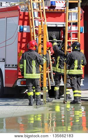 Firefighters In Action Take The Ladder From The Fire Engine
