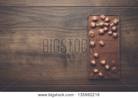chocolate bar with whole hazelnuts on wooden table