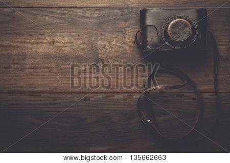 wooden background with retro still camera in case