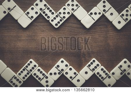 domino pieces on the brown wooden table with copy space