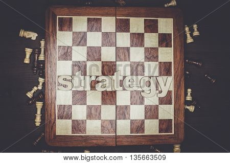 word strategy and chessmen on the brown wooden background