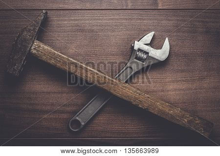 old rusty hammer and wrench on the wooden table