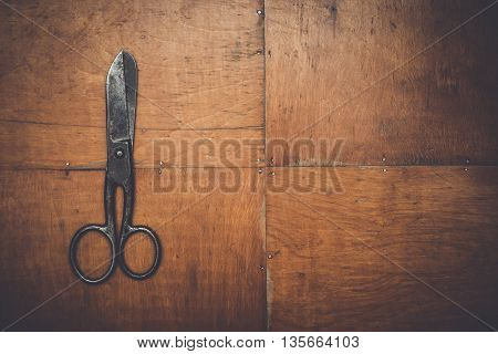 old black scissors on the wooden background