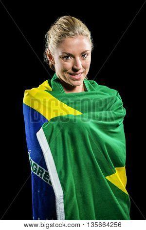 Athlete posing with brazilian flag wrapped around his body on black background