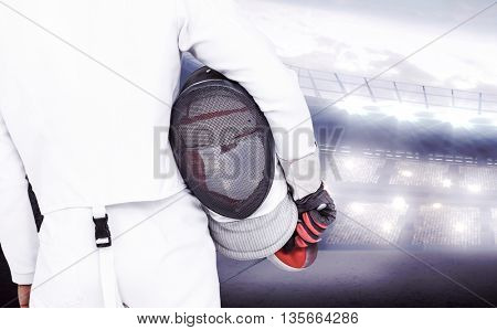 Rear view of swordsman holding fencing mask and sword against sports arena