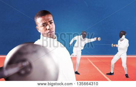 Swordsman practicing with fencing sword against digitally generated image of tracks