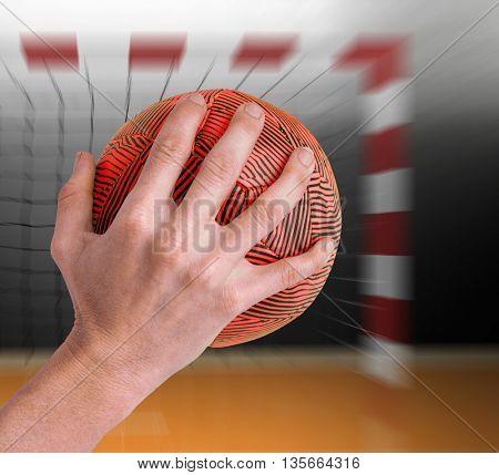 Sportswoman holding a ball against digital image of handball goal