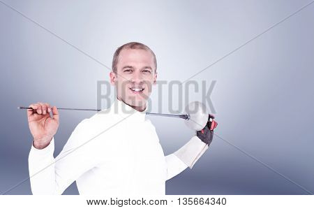 Swordsman holding fencing sword against grey vignette