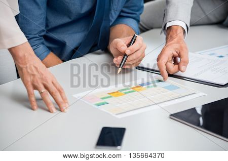Business partners discussing documents and ideas at meeting. Close up hands of businessmen and businesswoman working at office on a new project. Businessman hand showing charts and graphs.