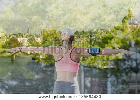 A beautiful athlete stretching her arms against river seine in paris