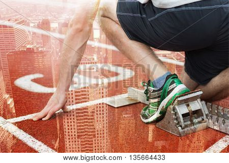 Mid section of a man ready to race on running track against image of a city landscape
