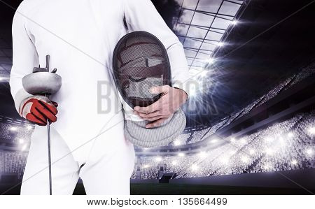 Swordsman holding fencing mask and sword against sports arena