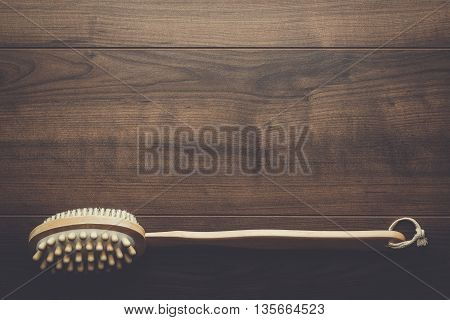 wooden massager brush on the brown table