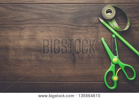 green measuring tape, scissors and pencil on the wooden table