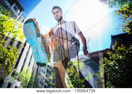 Handsome athlete running in the street against skyscraper