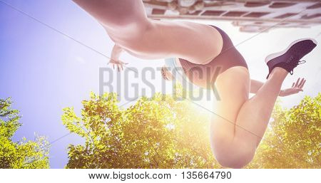 Low angle female athlete jumping against view of a house