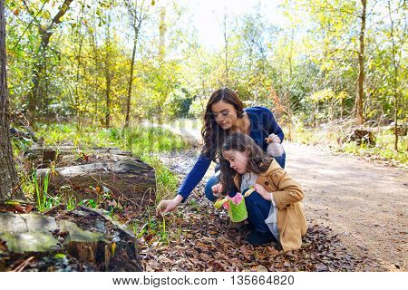 Mother and daughter in a park picking clover plants