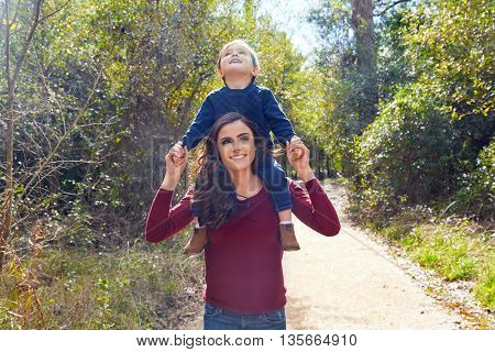 kid boy sitting on mother shoulders walking in the park trail