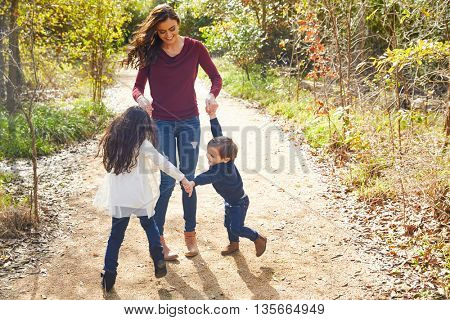 Family mother son and daughter turning circles holding hands at park