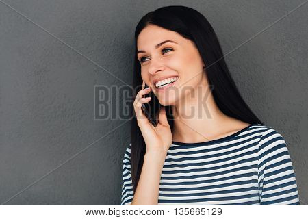 Good news from friend. Attractive young woman talking on the mobile phone and smiling while standing against grey background