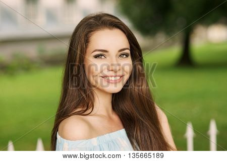 Young beautiful woman with long brunette hair and perfect smile. Happy girl posing in park and looking in camera