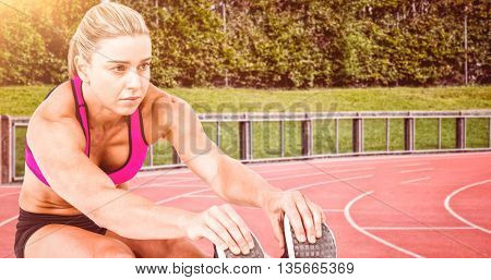 Female athlete sitting and stretching against race track