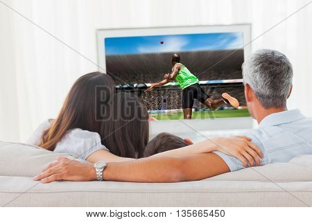 Rear view of sportsman throwing a shot against family watching television together on sofa