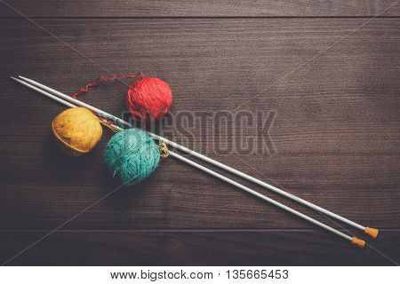 knitting needles and colorful ball of threads on the wooden background